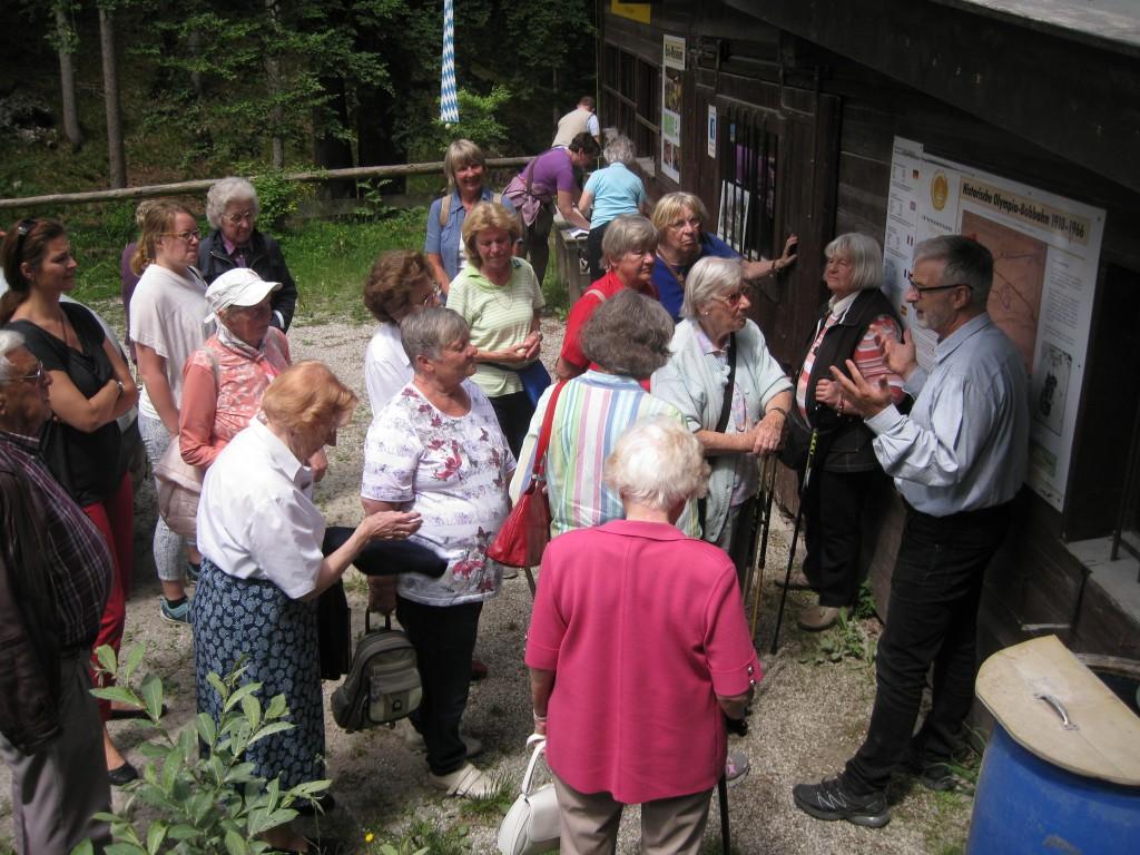Seniorinnen und Senioren mit dem ehemaligen Bobpiloten Wolfgang Hostmann vor dem Plan der Riesserseer Bobbahn.